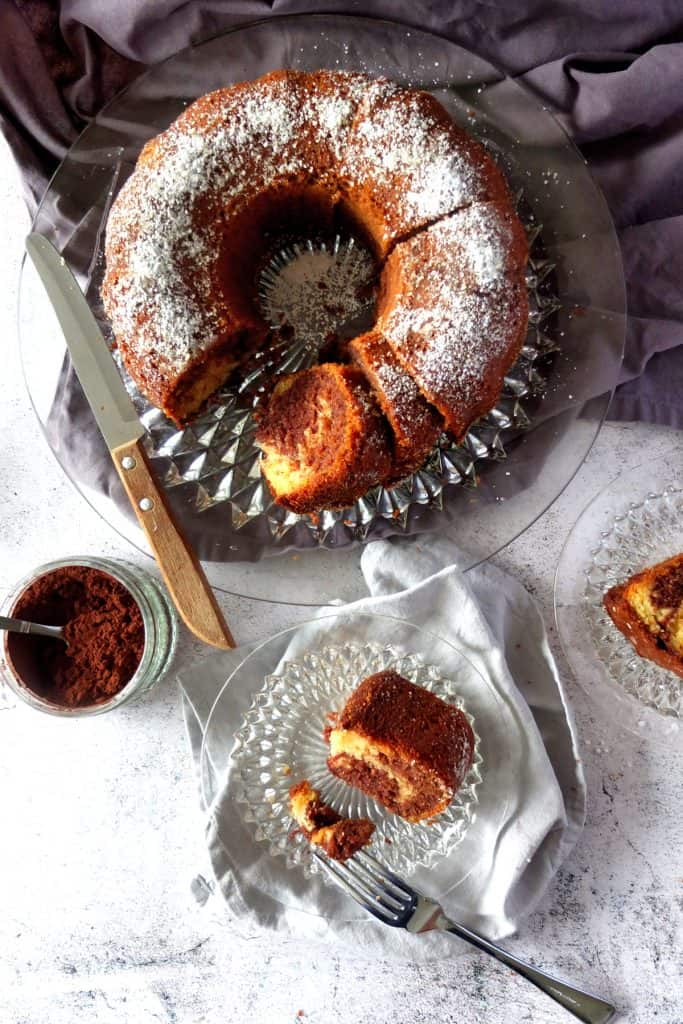 Black and White marble Cake on a white background. The cake is baked in bundt form and the cake plate sits on a grew towel. On the left you see a little pot of cocoa. The Cake is cut and on the cake plate you can see a knife with a wooden handle resting. A plate wlice of cake is resting on a napkin. A piece of cake is broken off iwth a fork.