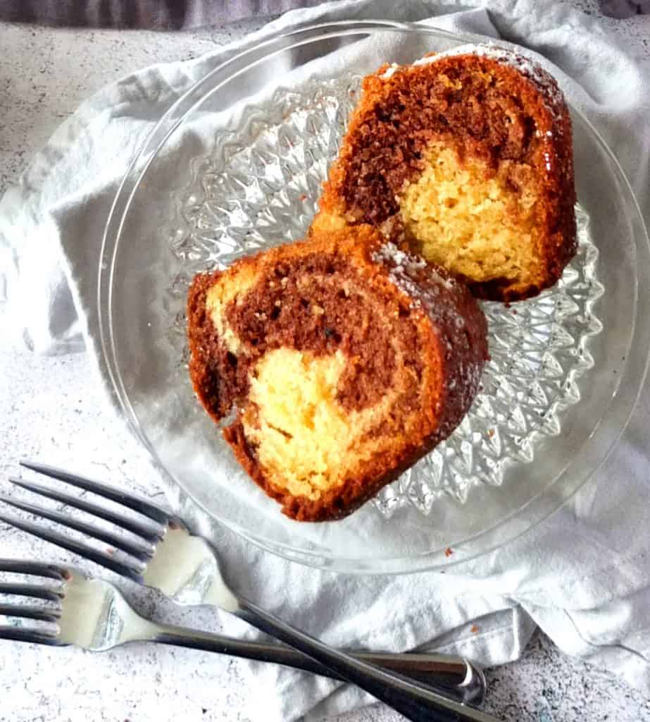 Two slices of marble cake on two glass plates. Below are two forks.