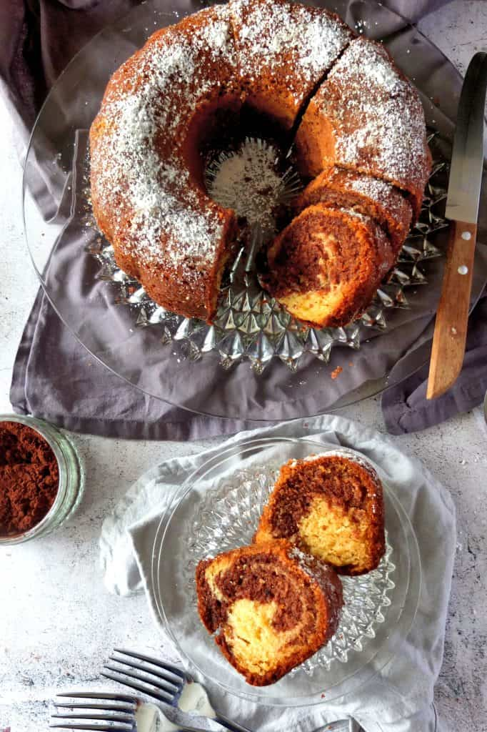 German Marble Cake on a glass cake plate. It is cut into slices. Two of the slices are resting on glas plates. On the left you can see a little glas container with cocoa powder.