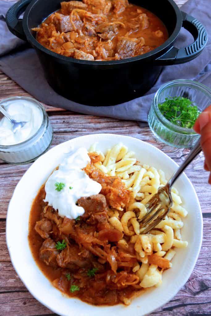 szegedin goulash on a white plate on a wooden background with spätzle. A hand holding a fork is digging into it. In the background you can see a sauce pan with the goulash. Two little pots with parsely and sauerkraut.