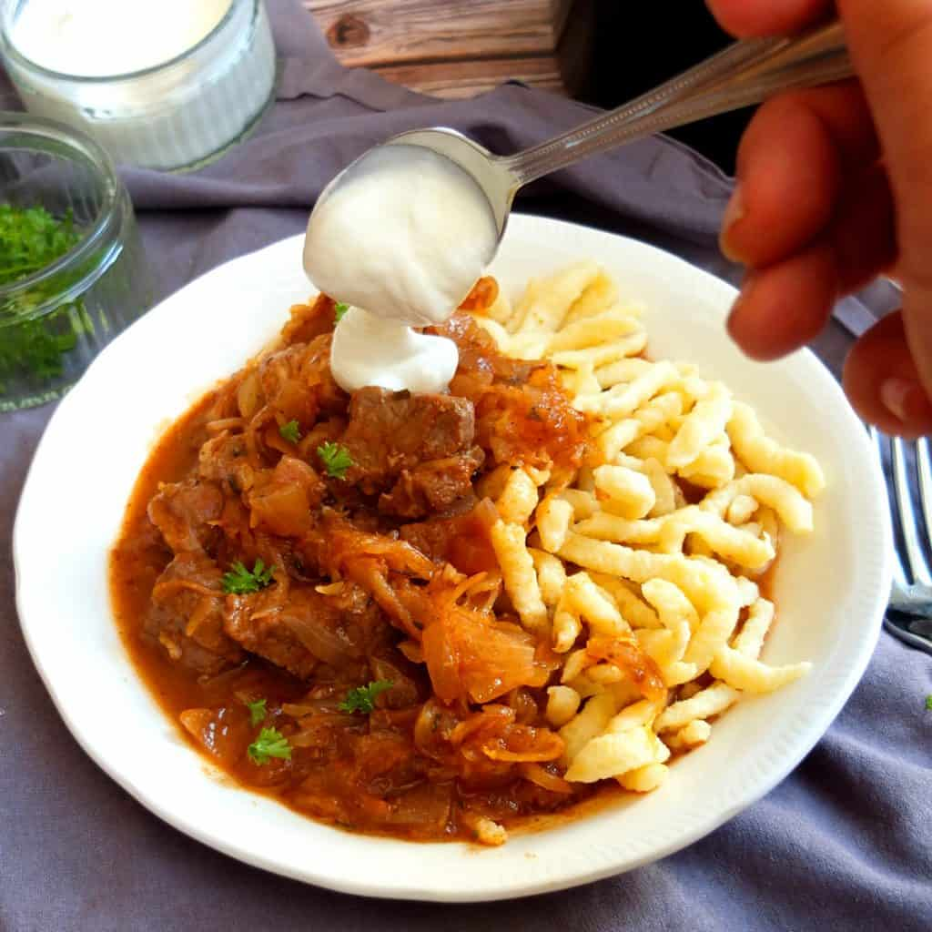 szegedin goulash on a white plate on a wooden background with spätzle. A spoon is adding a dollop of sourcream to the stew