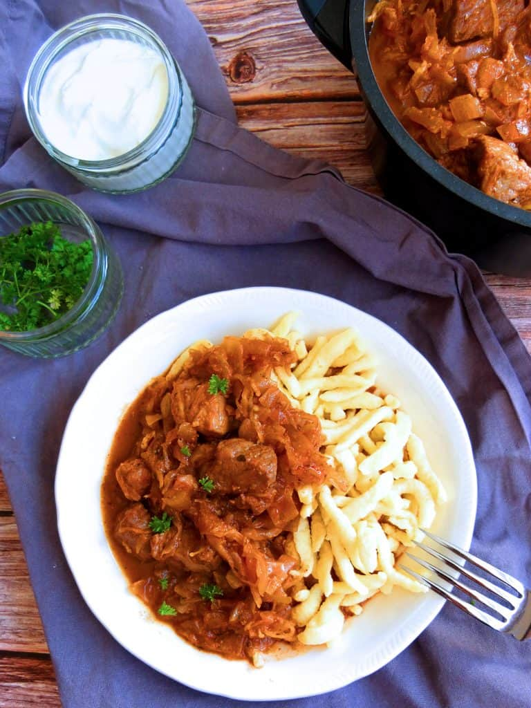 szegedin goulash on a white plate on a blue towel on a wooden background with spätzle. A fork is reasting on the plate In the background you can see a sauce pan with the goulash. Two little pots with parsely and sauerkraut.
